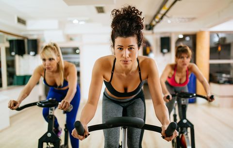 Três mulheres praticando ciclismo indoor