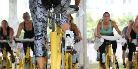 professora de costas é observada por alunos durante aula de ciclismo indoor