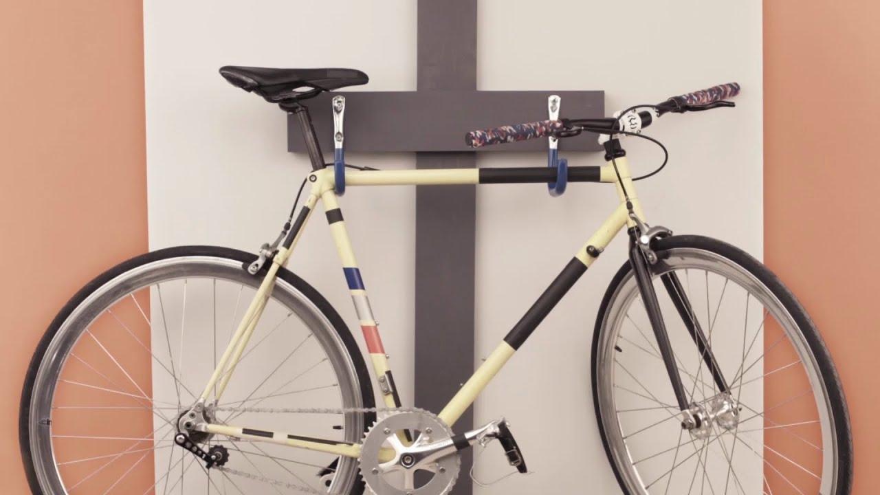 Bicicleta sustentada na parede por suportes em formato de ganchos