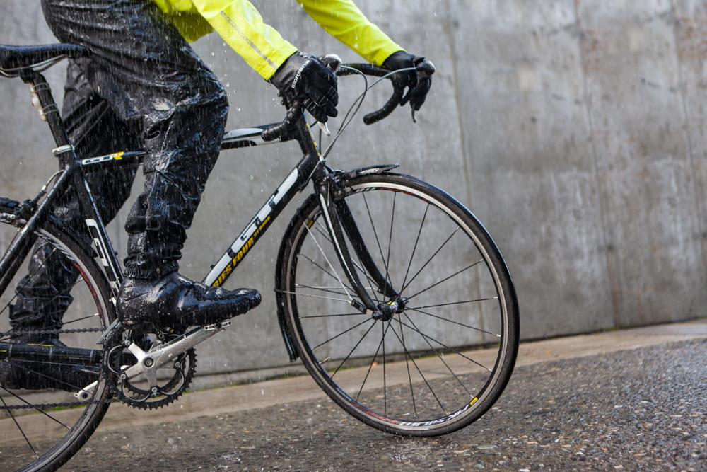 Ciclista pedalando de bicicleta na chuva