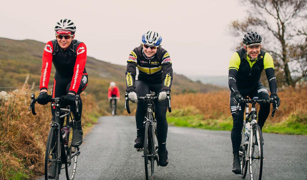 Três amigos pedalando de bike.