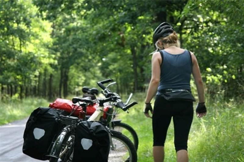 Mulher caminha ao lado de sua bicicleta equipada para o cicloturismo
