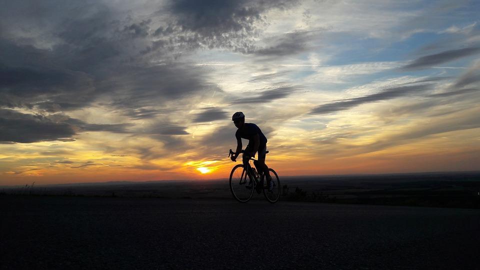 Homem pedala no final de tarde.