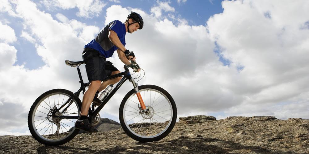 Homem sobe morro de rochoso pedalando de montain bike