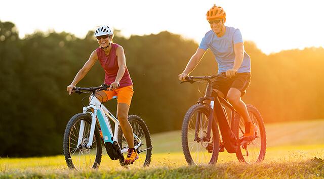 Homem e mulher pedalando