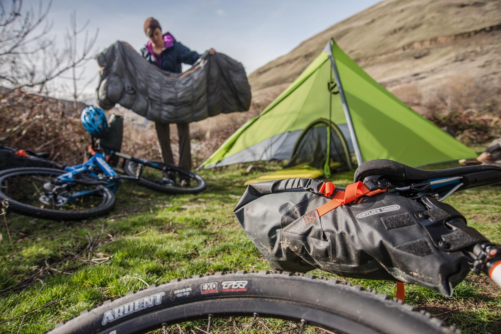 Mulher prepara o saco de dormir durante o Bikepacking