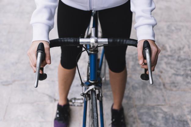 Mulher em pé sobre a bicicleta