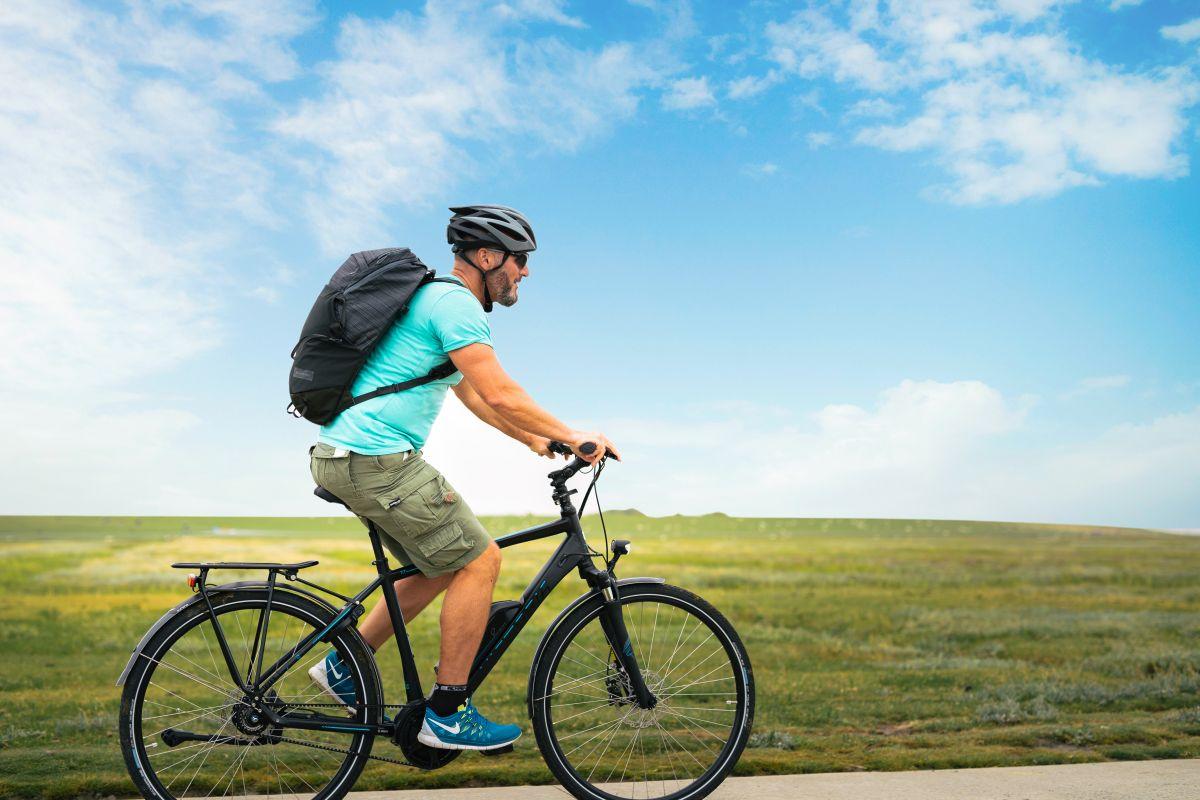 Homem pedalando ao lado de um campo gramado.