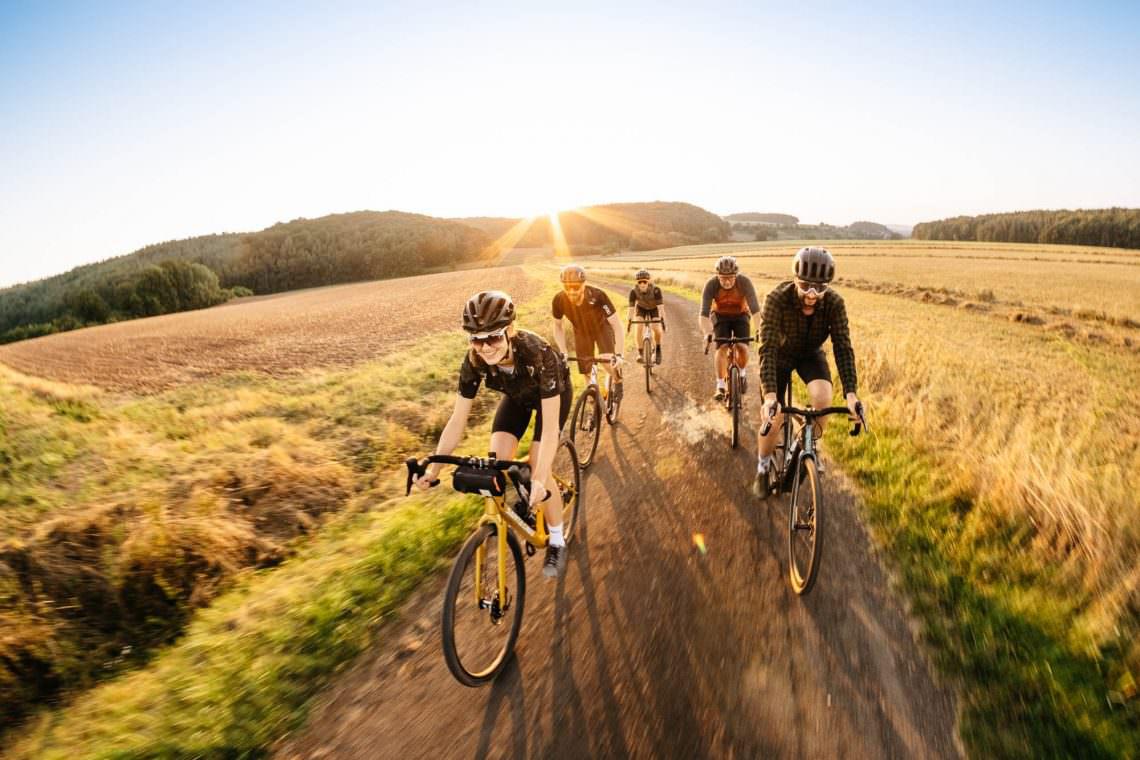 Ciclistas praticam pedal em grupo no campo.
