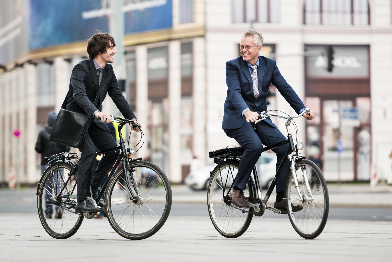 Dois homens de terno indo ao trabalho de bicicleta