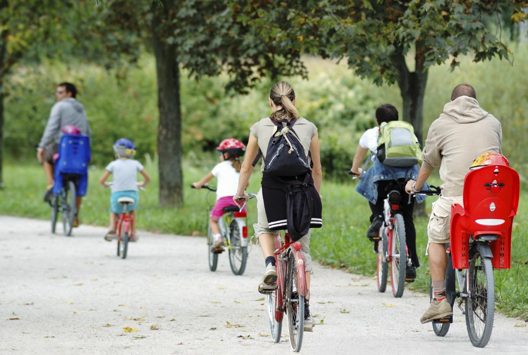 Família pedalando de bicicleta em um parque.