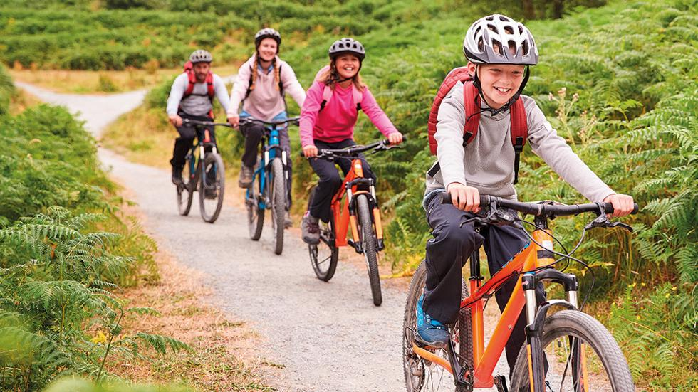 Família pedalando com o garoto à frente sorrindo.