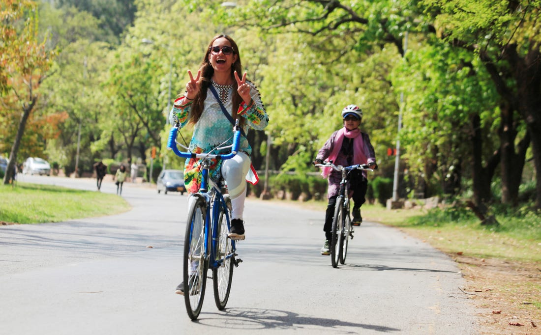 Mulher pedalando e sorrindo