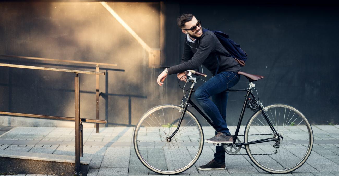 Homem para sobre a bicicleta sorrindo e apreciando a paisagem