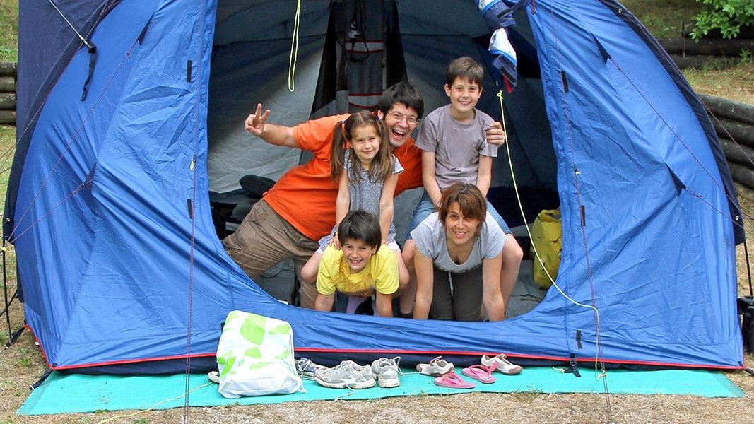 Família dentro de uma barraca para chuva