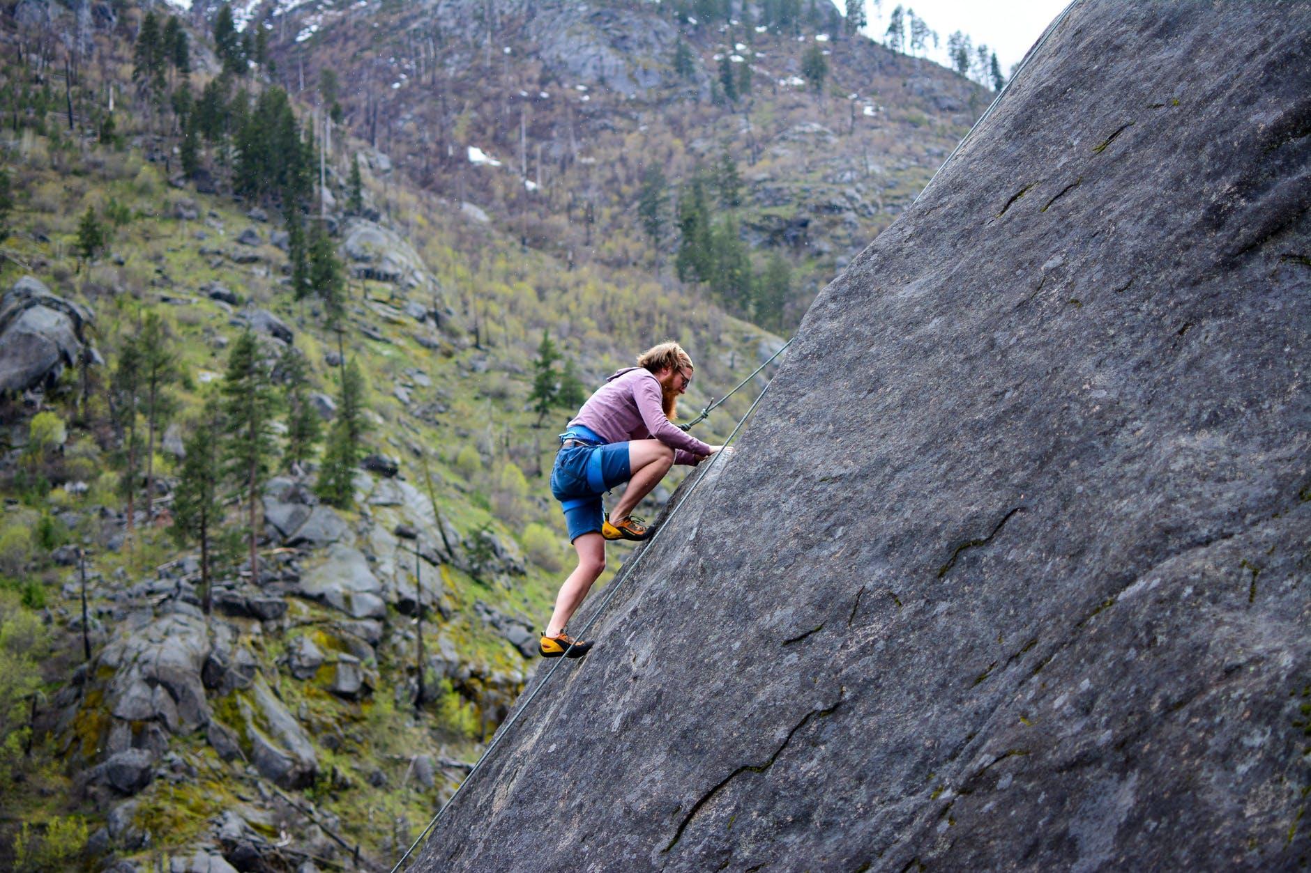 Homem escalando uma pedra