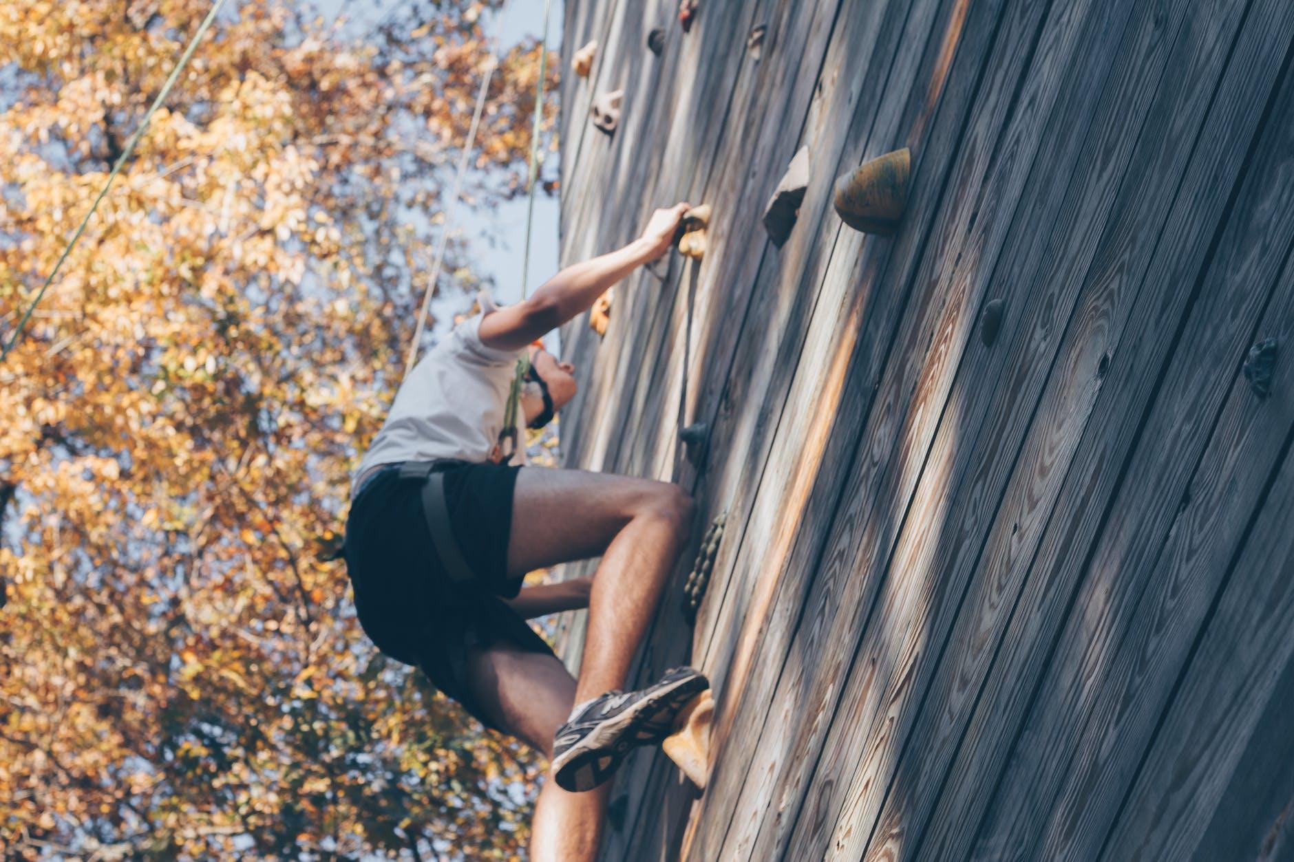 Homem escalando parede de escalada.