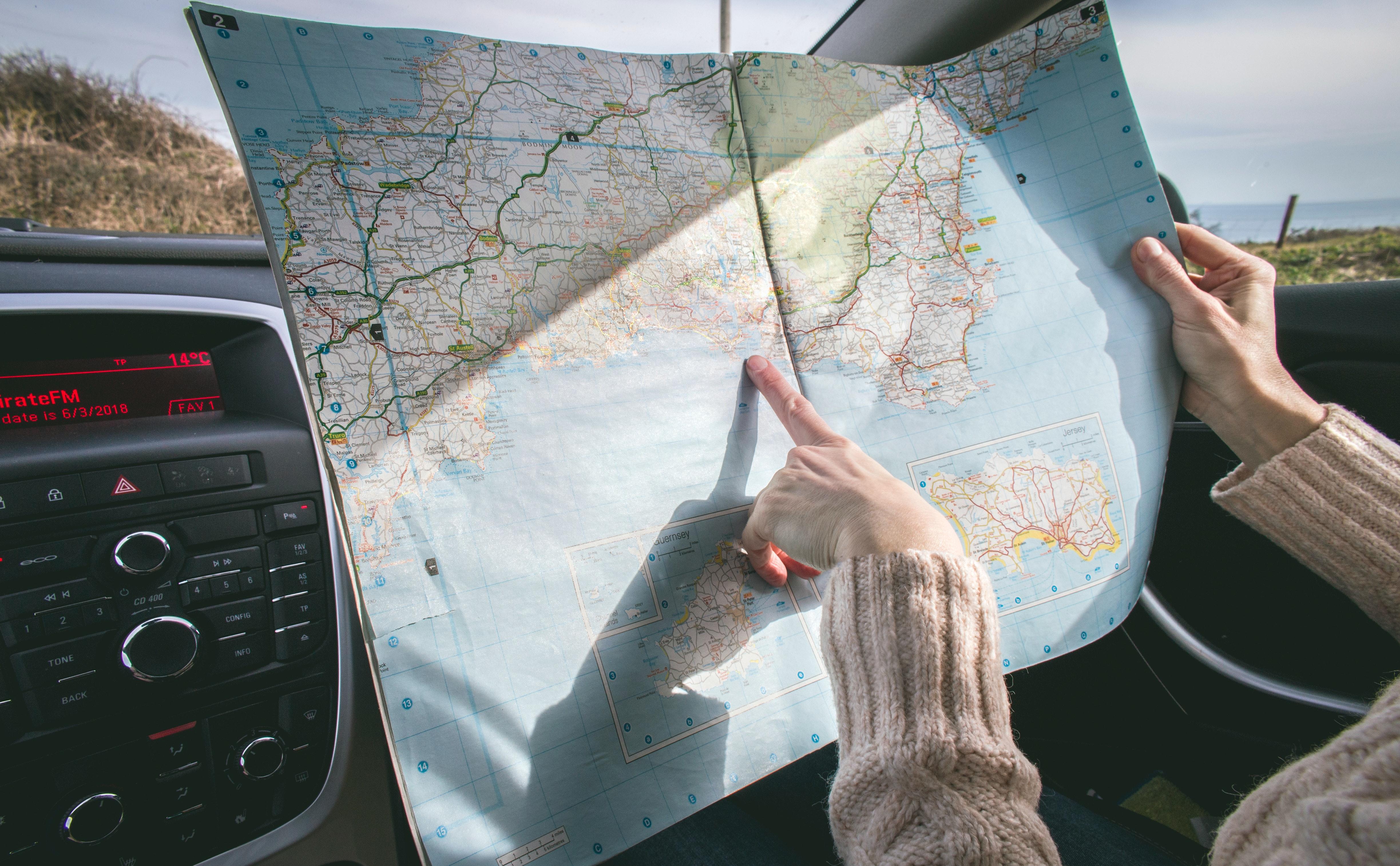 Mulher aponta para o mapa dentro do carro