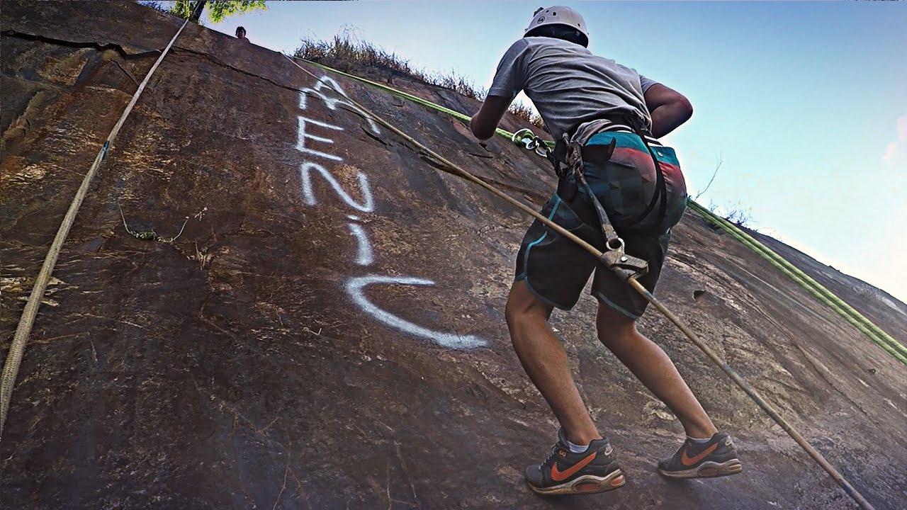 Homem descendo parede rochosa de rapel