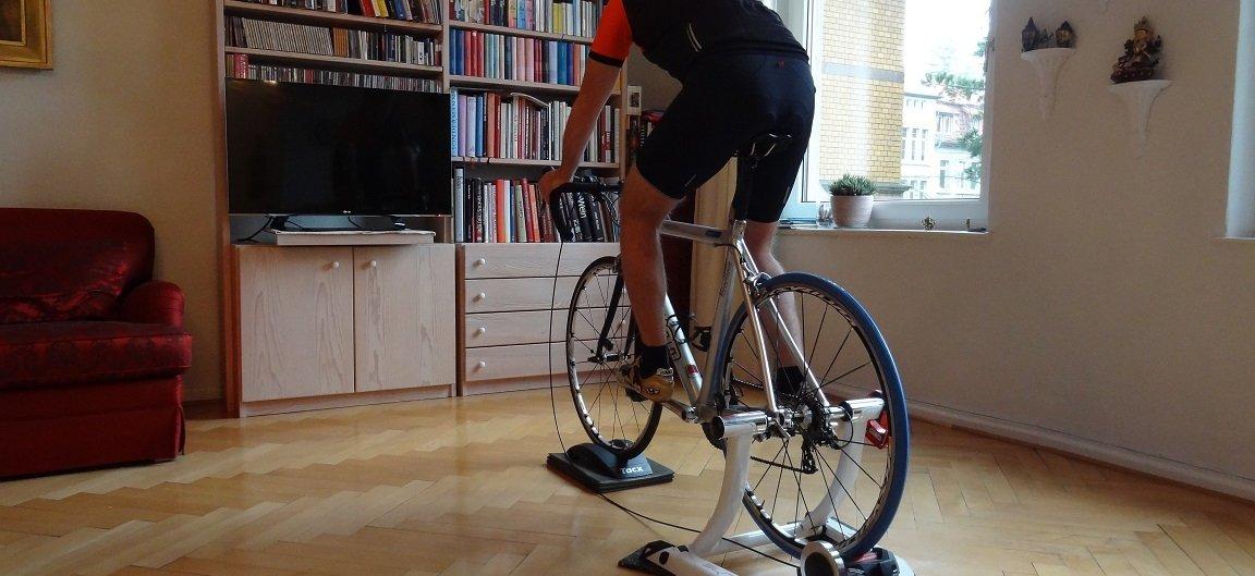 Homem pedalando na sala de sua casa usando um rolo de treino