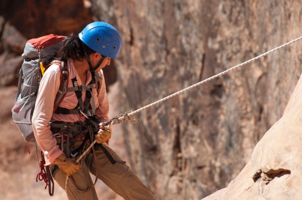 mulher usando equipamentos de proteção e praticando escalada