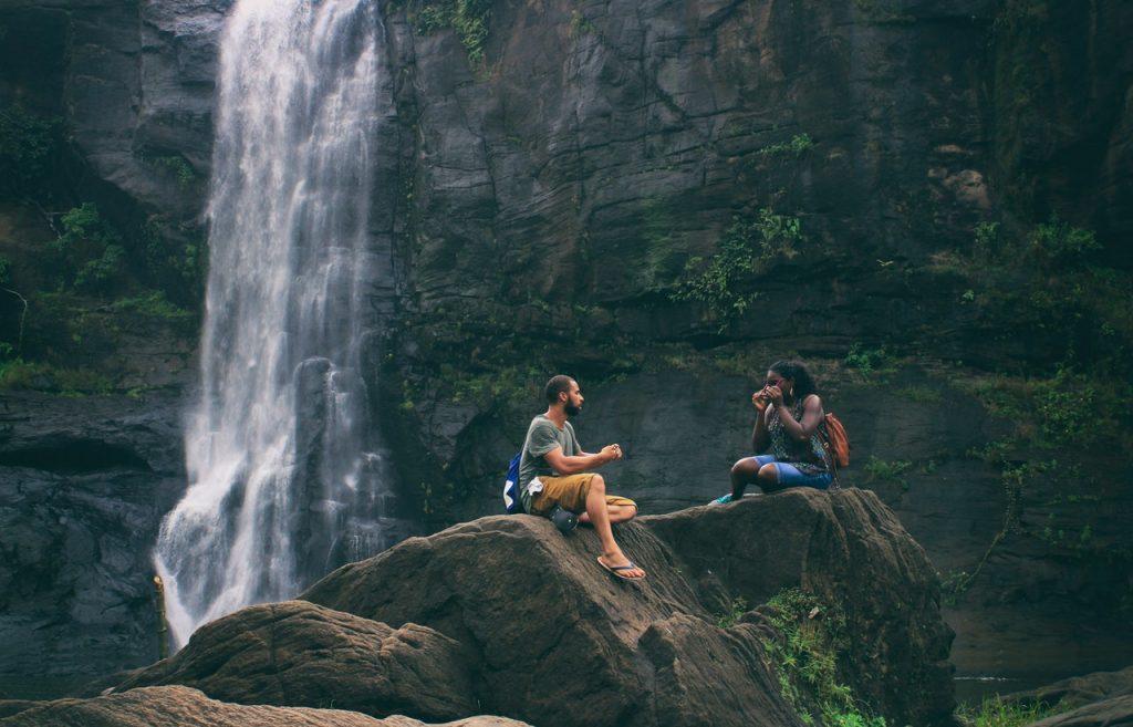 um homem e uma mulher sentados na pedra de uma cachoeira