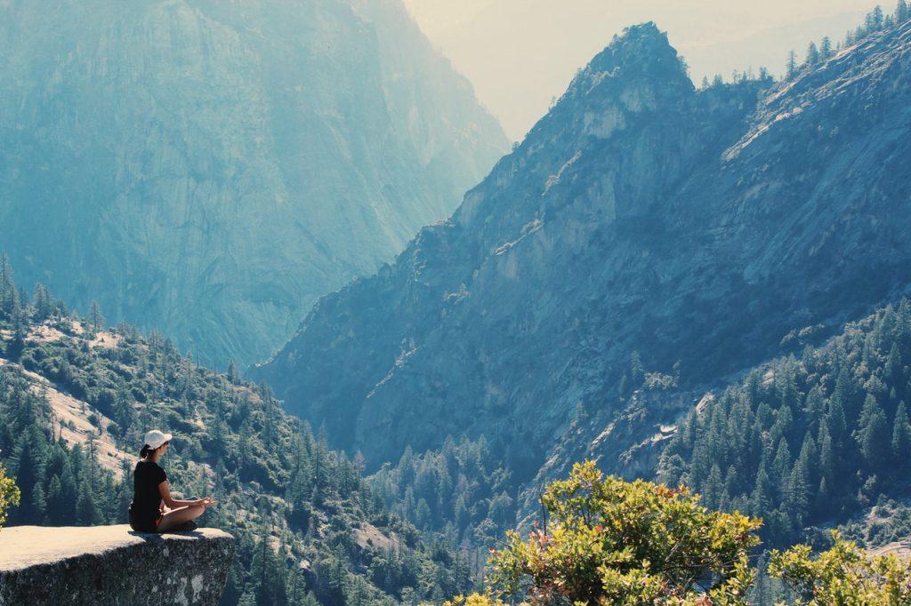mulher meditando em uma pedra em meio a natureza