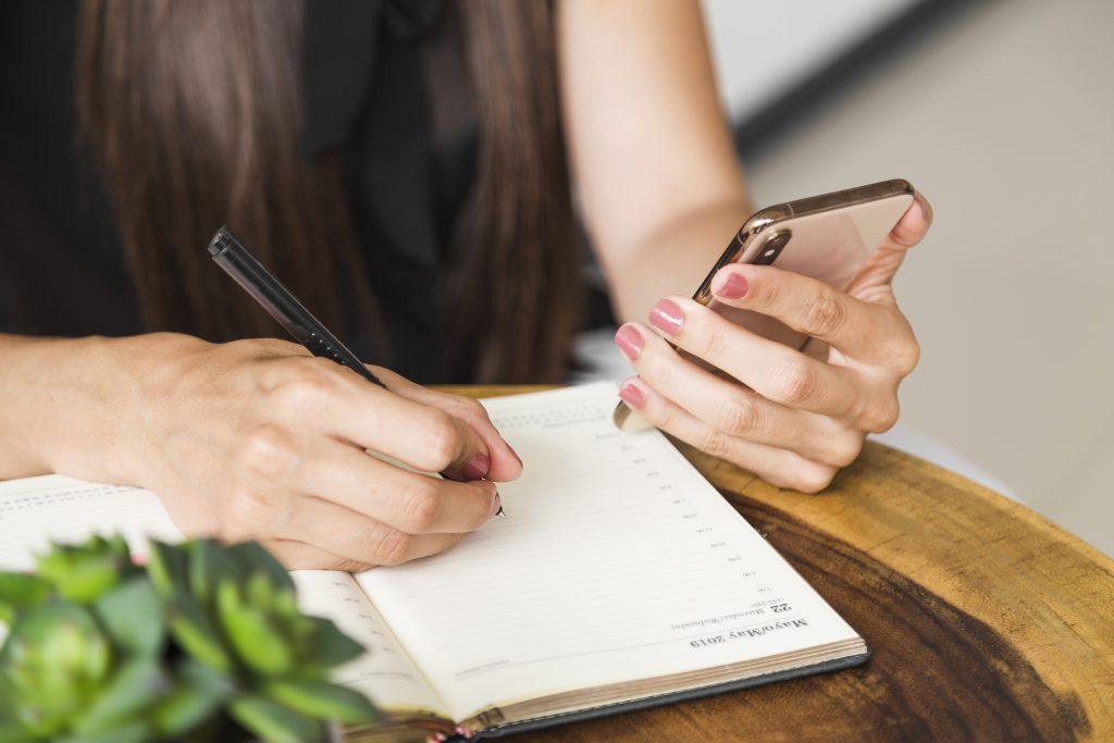 mulher usando o celular e agenda para planejar tempo para se desconectar do trabalho