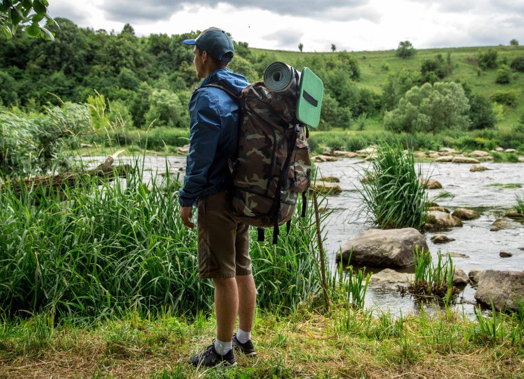 homem carregando mochila de acampar admirando a natureza