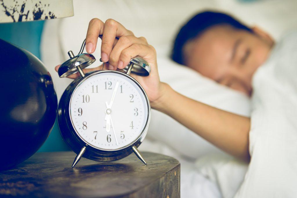mulher  apresentandoo sinais de overtraining no ciclismo deitada na cama com problemas para dormir