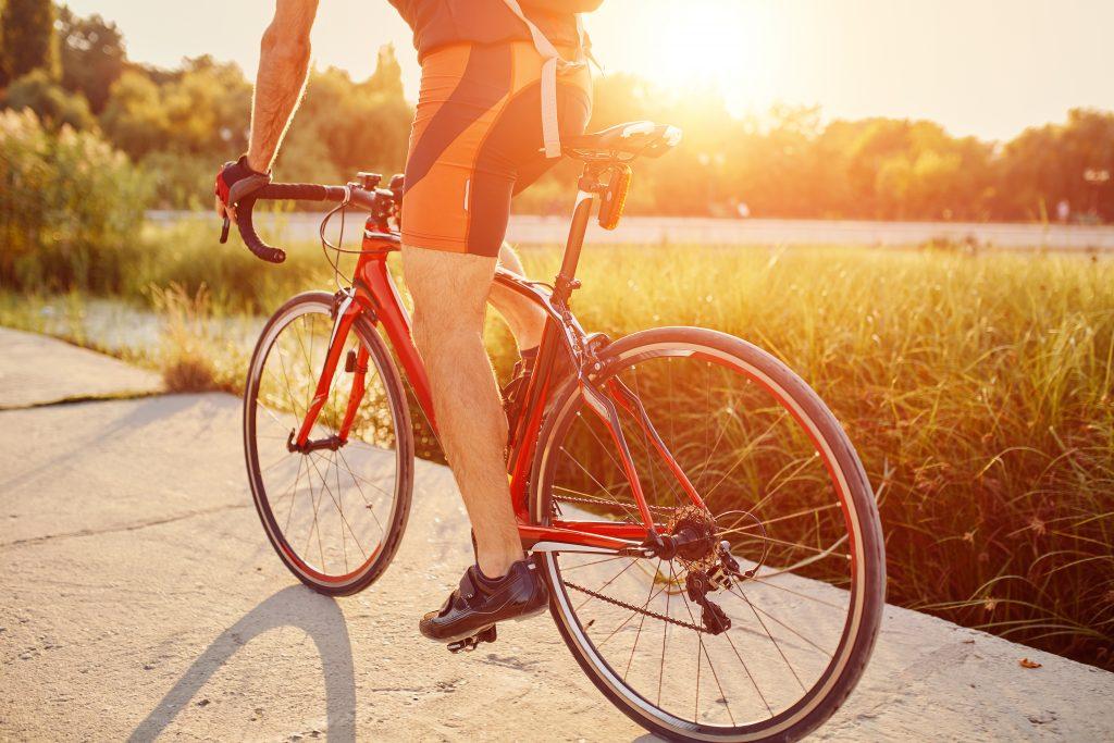 ciclista andando de bicicleta em uma pista de bicicleta perto de um lago