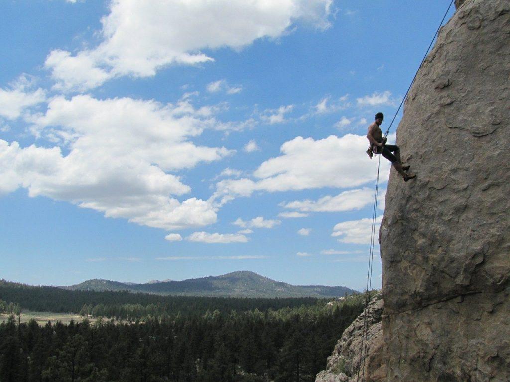 Homem praticando rapel em atividades verticais