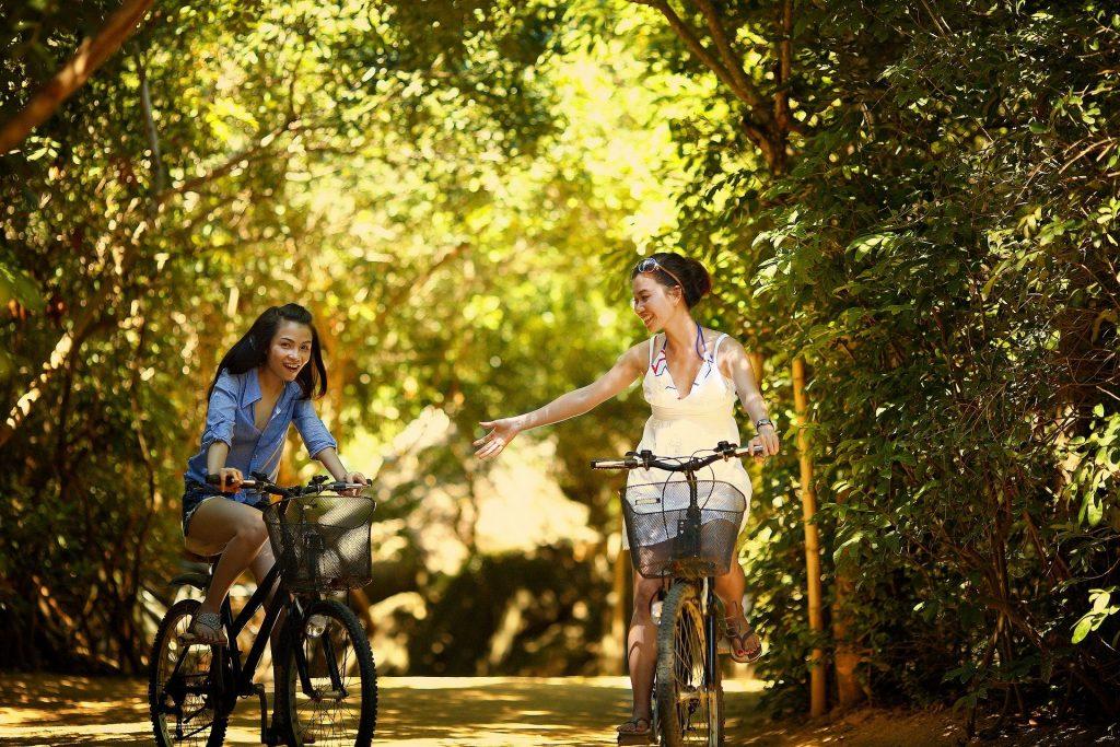 Moças praticam ciclismo juntas