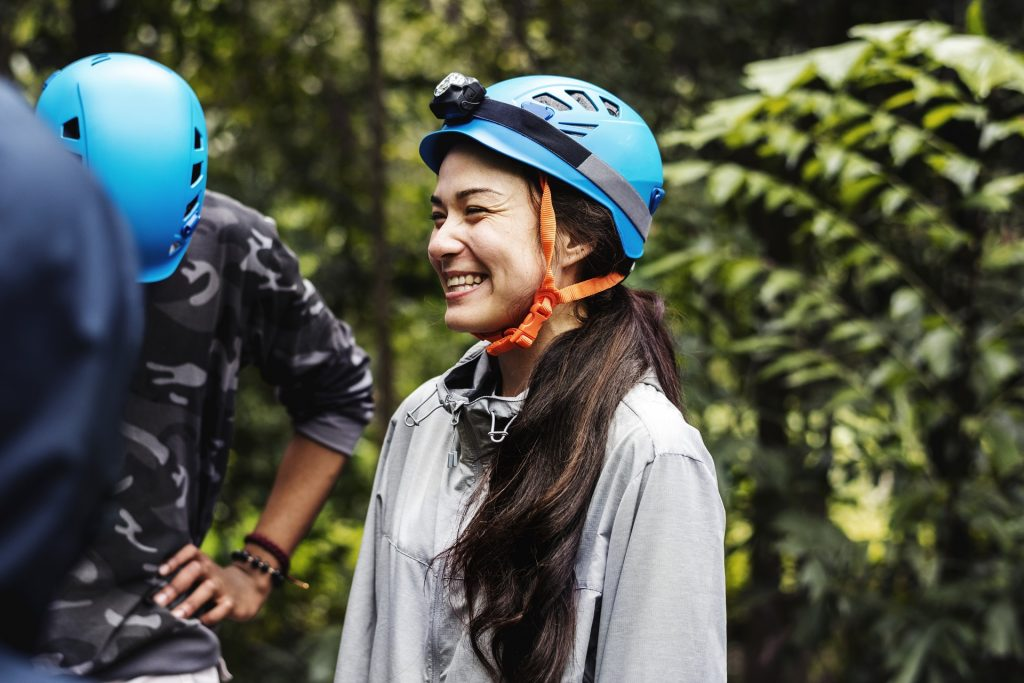 Mulher usando capacete com lanterna de cabeça