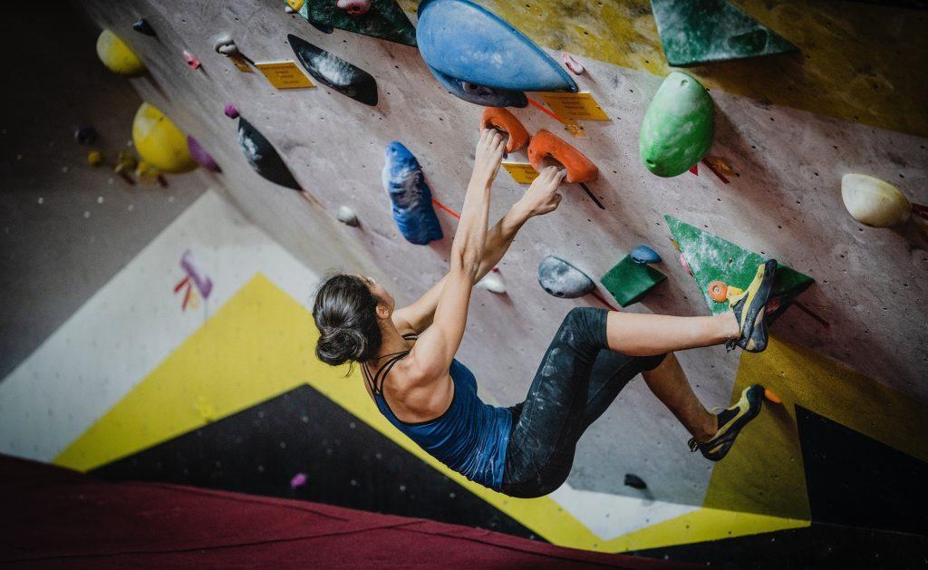 Mulher na parede de treinamento para escalada