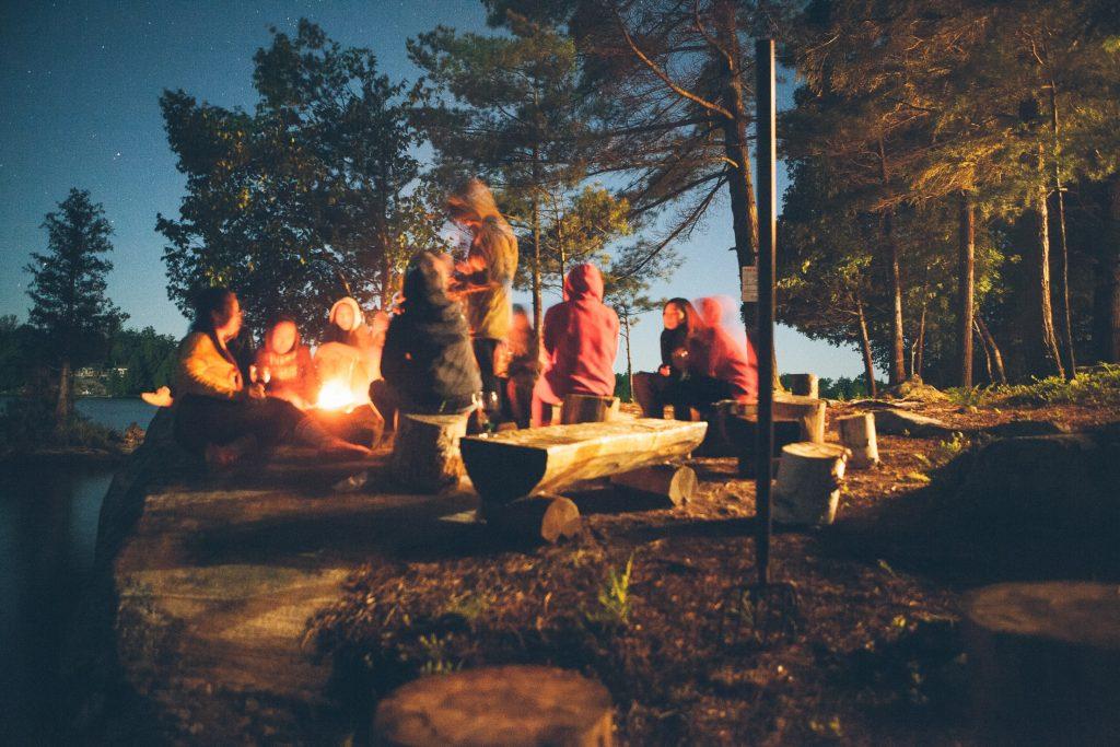 Grupo de pessoas em volta da fogueira perto de rio e floresta