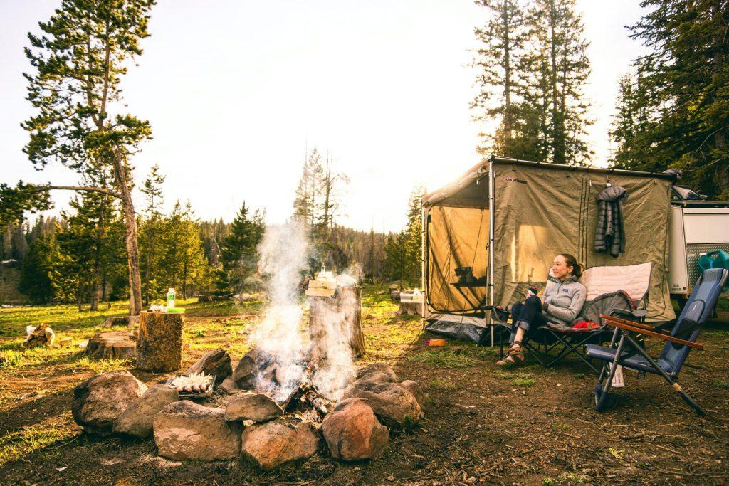 Mulher em camping com fogueira entre pedras