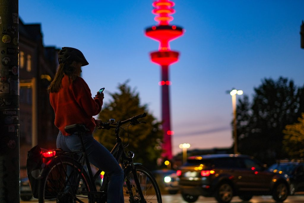 Mulher com capacete sai para pedalar à noite em bicicleta com farol traseiro