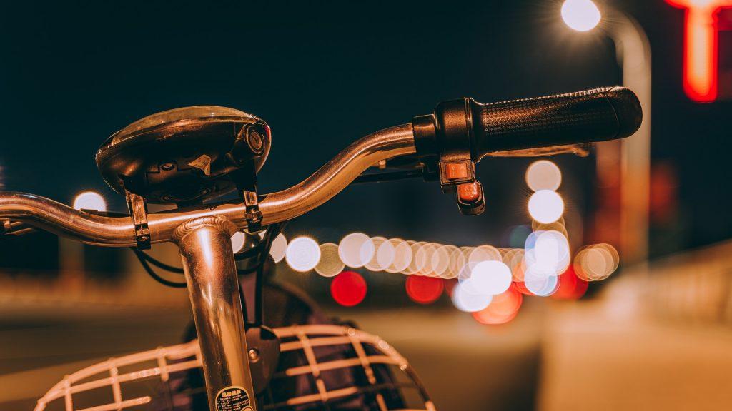 Guidão de bicicleta retrô com farol apagado em meio à cidade durante à noite
