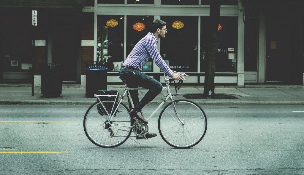 Homem de camisa xadrez e calça vai trabalhar de bicicleta branca