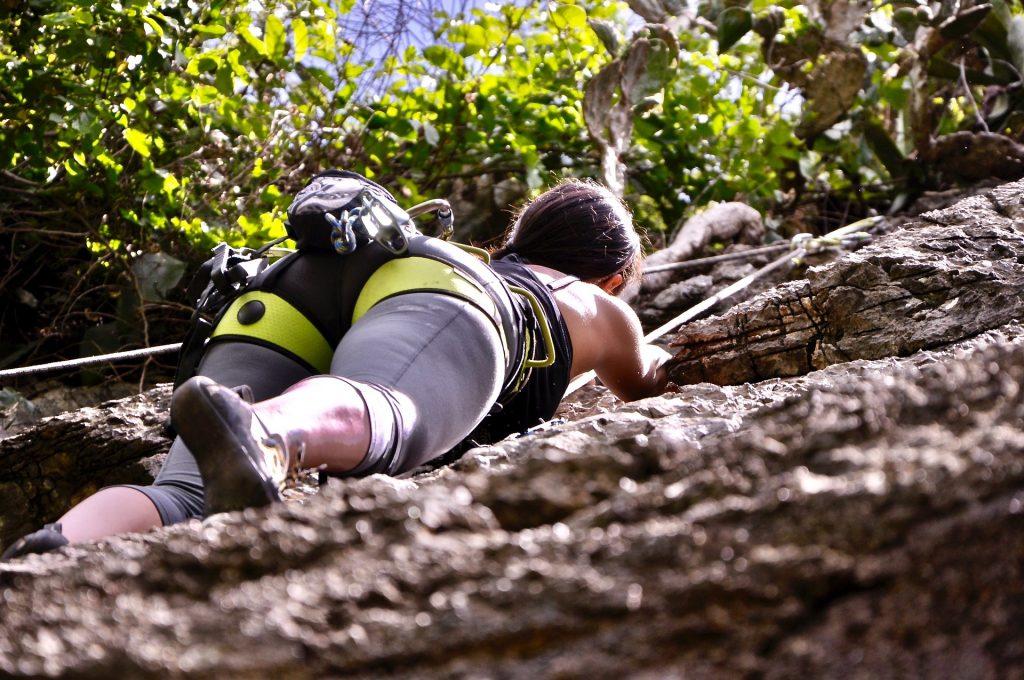 Mulher na pedra faz um treinamento para escalada e pensa em seu próximo movimento