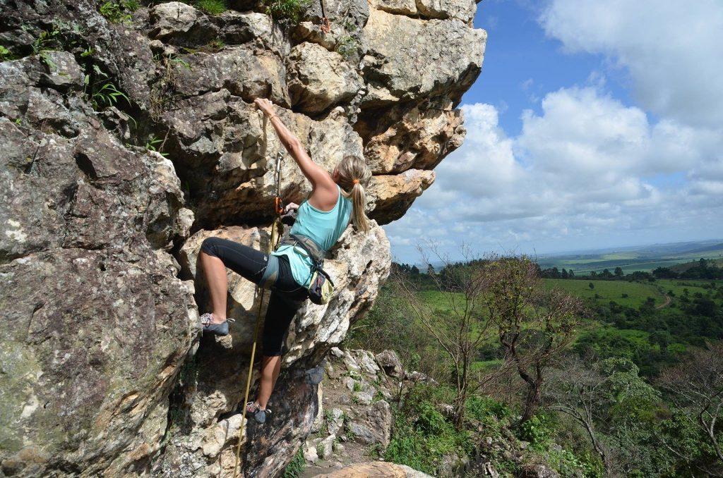 Mulher loira de calça preta e blusa azul em treinamento para escalada em rocha