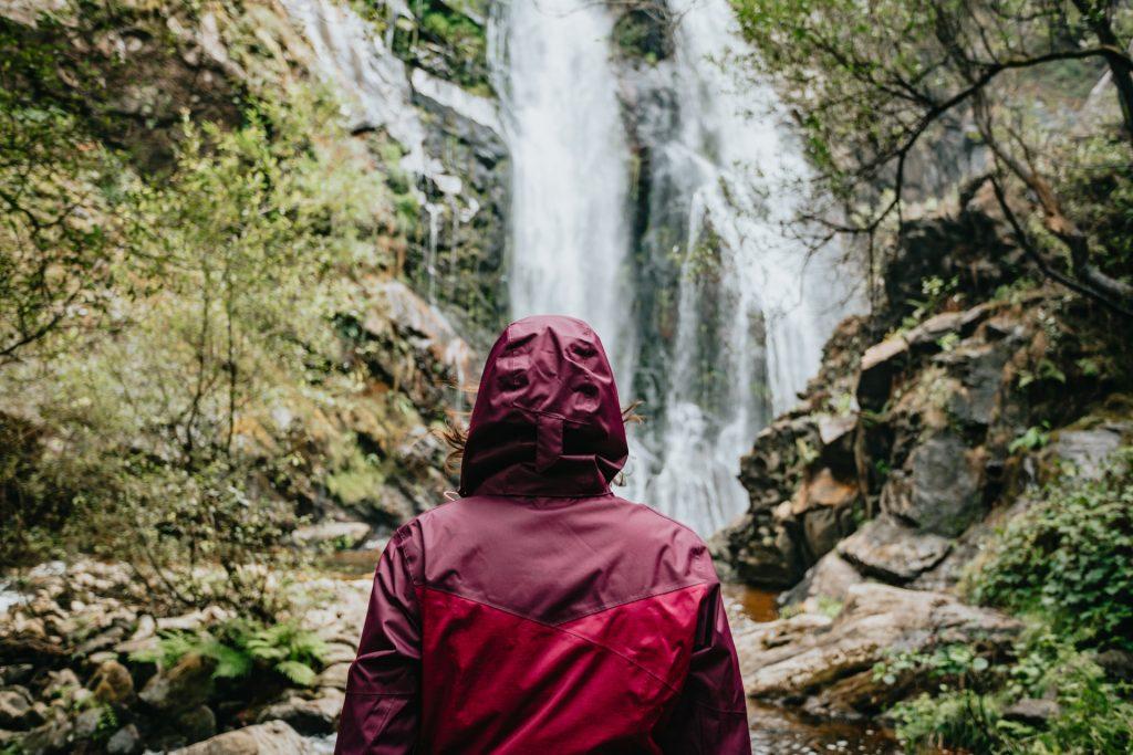 Pessoa com jaqueta impermeável na cor vinho em frente à cachoeira pode fazer trekking na chuva sem se preocupar com a água