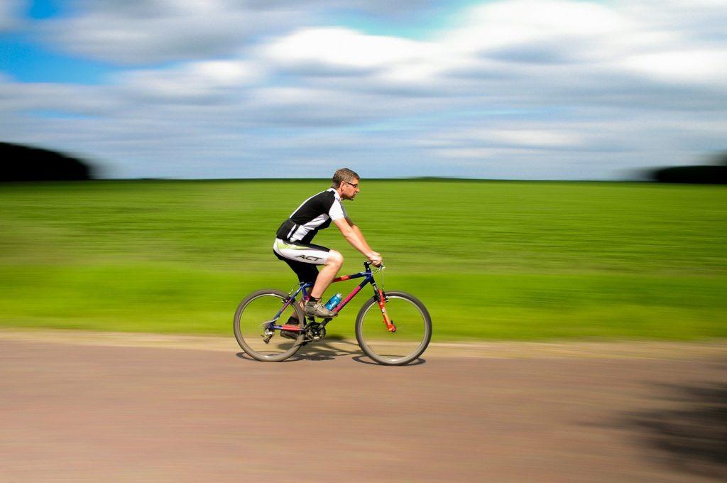 Ciclista andando de bicicleta vermelha no campo deve se proteger do sol