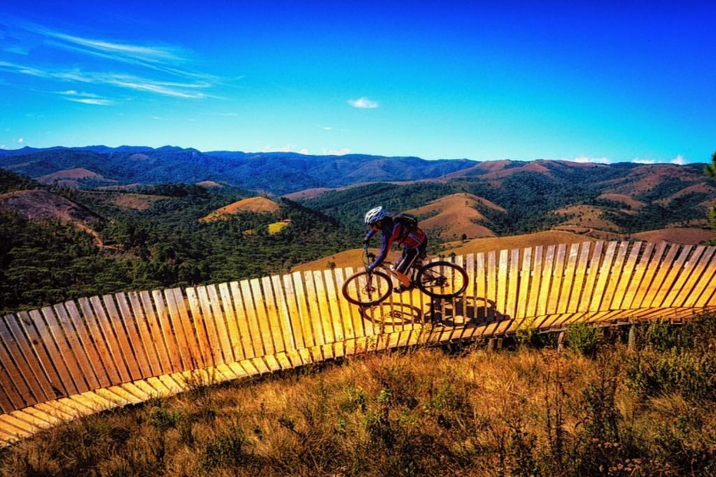 Ciclista passando por uma ponte no Zoom bike park em meio às montanhas