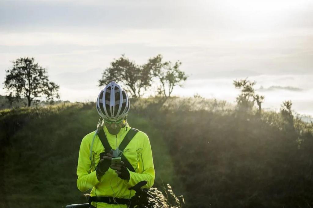 Ciclista, em meio à natureza, usando fone enquanto escuta podcasts do Deezer