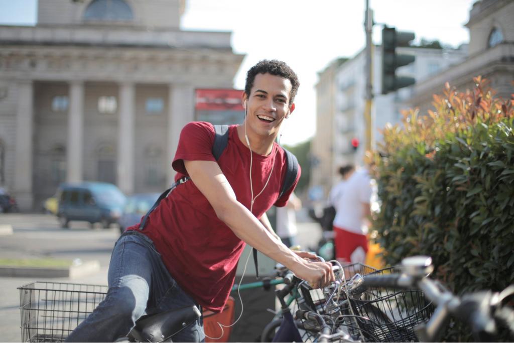 Homem Vestindo Camisa Vermelha Em Pé De Bicicleta com fone