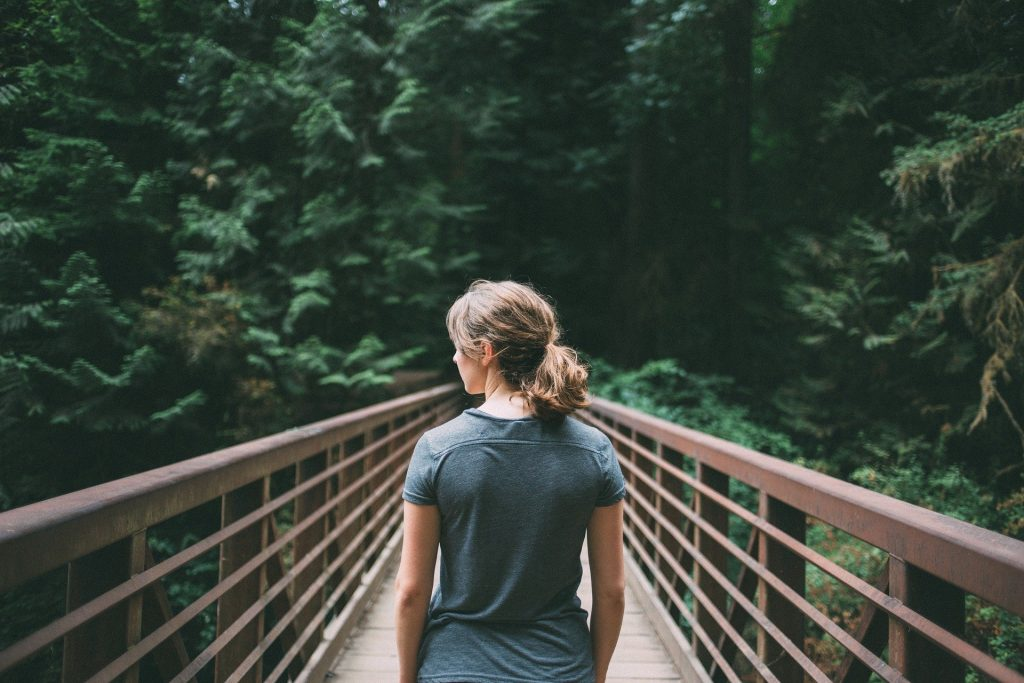 Mulher em meio a natureza, de frente para uma ponte