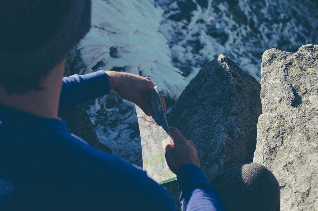 Homem sentado em local rochoso segurando uma mapa
