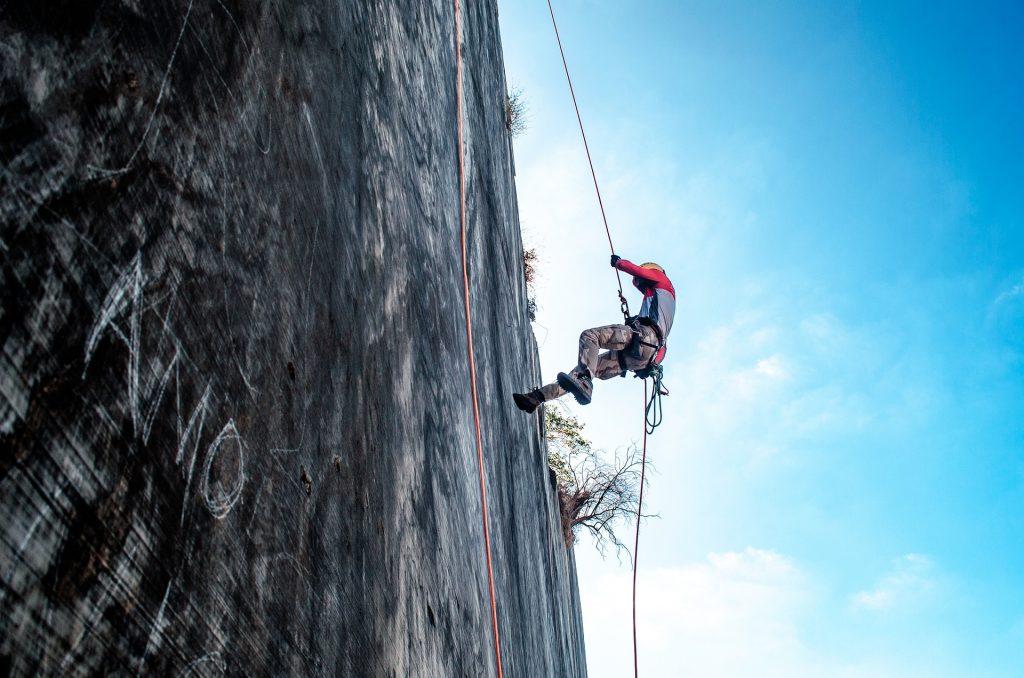 Mulher praticando rapel em uma parede em meio a natureza